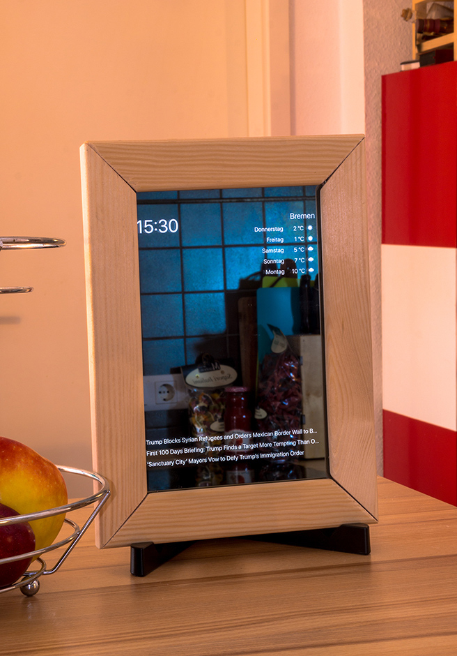 Photograph of a wooden framed mirror with weather and calendar events projected onto the glass